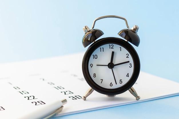 青のミニ目覚まし時計、カレンダー、ペンのクローズアップ