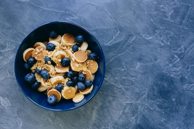 ミニパンケーキシリアル、メープルシロップハニーとブルーベリーの濃い青のボウルに入ったミニパンケーキのクローズアップ。