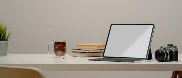 Закройте минимальный рабочий стол с ноутбуком и камерой Premium Фотографии