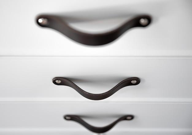 黒のハンドル、キッチンキャビネット、詳細を備えたミニマルな白い家具のクローズアップ。