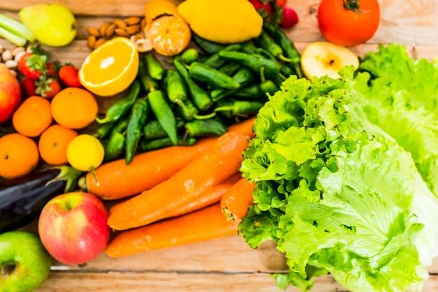 Закройте смешанные и цветные сезонные овощи и фрукты на деревянном столе