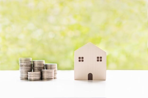 Закройте модельный дом и деньги на белом столе. соберите деньги, чтобы купить новый дом.