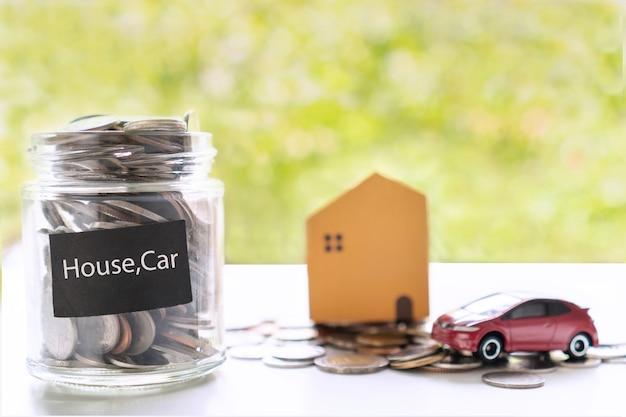 모델 하우스와 녹색 bokeh 배경에 흰색 테이블에 돈을 닫습니다. 새 집, 주택 비용, 계정, 저축 및 투자 개념을 구입하기 위해 돈을 모으십시오. 플랫 레이