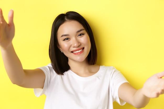 스마트 폰, 미소, 노란색 배경 위에 서있는 예쁜 여자의 모바일 카메라보기에 selfie를 복용하는 현대 아시아 여자의 닫습니다.