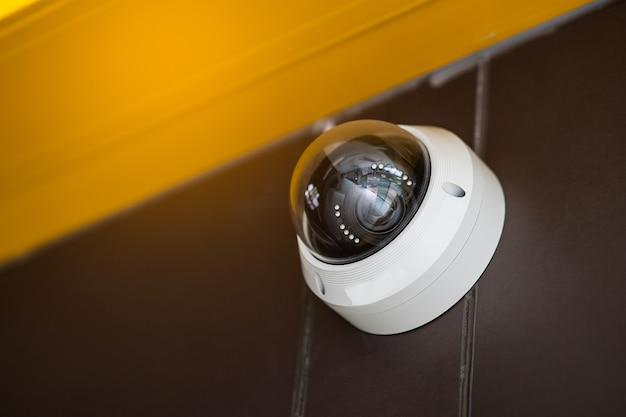 Закройте вверх современной камеры видеонаблюдения на стене. концепция наблюдения и мониторинга.