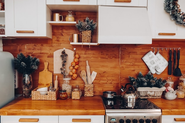 Крупный план современной уютной кухни в белых и коричневых тонах с вещами, плитой и декоративными еловыми ветками. рождественские украшения.
