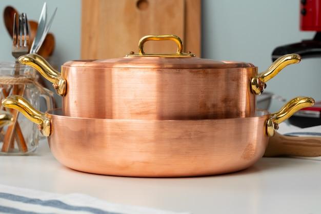 銅の調理器具とモダンなキッチンインテリアのクローズアップ