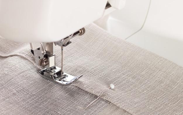Крупный план прижимной лапки современной швейной машины и иглы для шитья одежды.