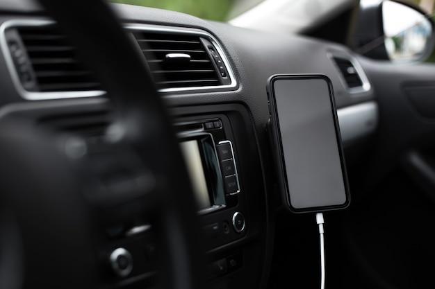 Крупный план современного смартфона с пустым экраном на зарядке внутри автомобиля.