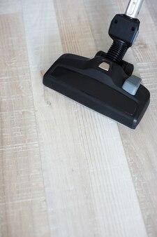 木の床を掃除する現代の掃除機のクローズアップ