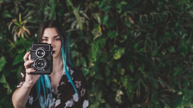 빈티지 카메라로 사진을 찍는 현대 여성의 근접 촬영