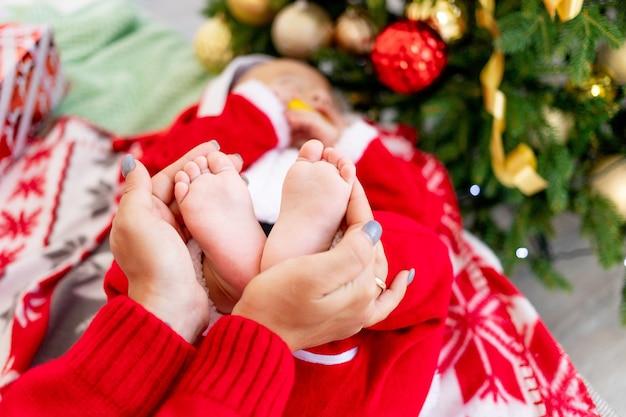 빨간 하트 모양의 장식, 새해와 크리스마스의 개념으로 크리스마스 트리에서 아기의 발을 잡고 있는 엄마의 클로즈업