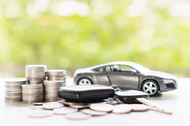 緑のボケ味の背景に白いテーブルの上の車のキーとお金とモデル車のクローズアップ