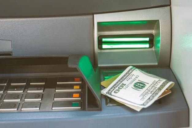 은행 카드가 있는 돈의 클로즈업은 atm에 놓여 있습니다.