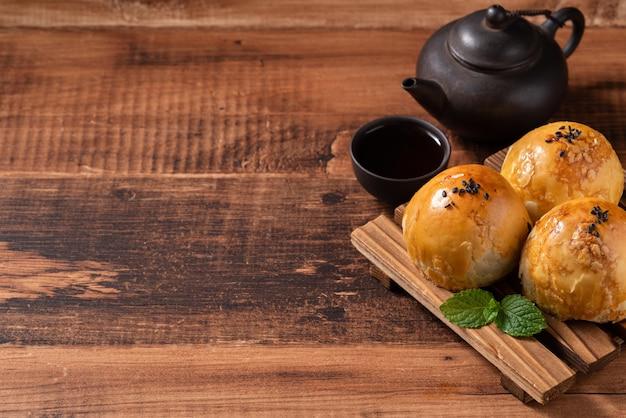 月餅ヨークペストリー、木製のテーブルの背景に中秋節の休日の月餅のクローズアップ