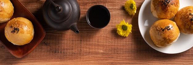 木製のテーブルの背景に月餅卵黄ペストリー、中秋節の休日の月餅のクローズアップ