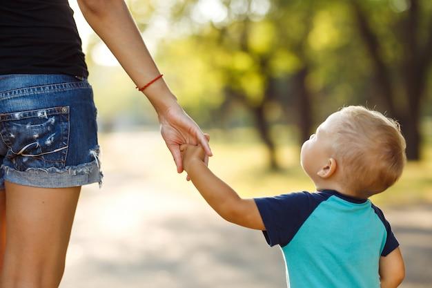 Закройте руки матери и ребенка на закате. мама и сын гуляют в парке.