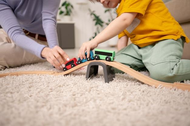 カーペットの上に座っておもちゃの鉄道でおもちゃの列車で遊んでいる母と息子のクローズアップ