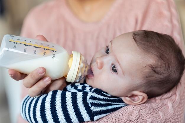 自宅のソファに座っている間、哺乳瓶で彼女の赤ん坊の息子を養っている母親のクローズアップ。
