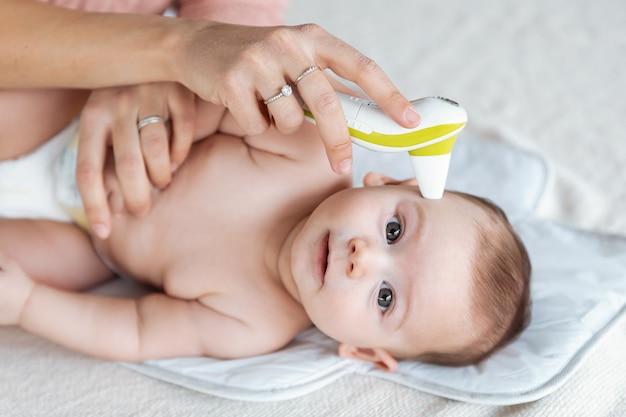 집에서 적외선 온도계로 아기의 온도를 측정하는 어머니의 클로즈업.