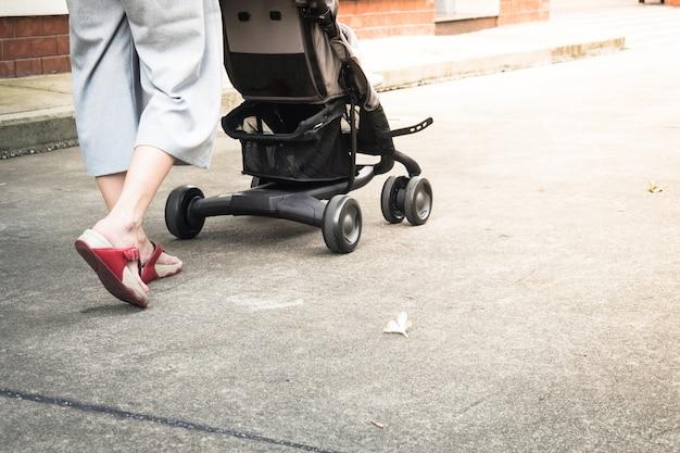 유모차와 함께 산책하는 어머니의 닫습니다. 엄마와 아이 개념의 여행 배경