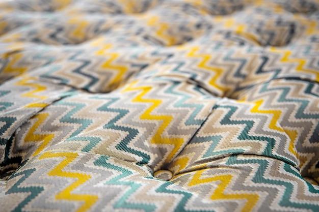 Крупным планом пестрый мягкий диван текстуры с затонувшими кнопками