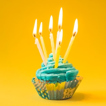 Close-up of muffin with burning candles on yellow background