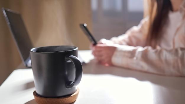 전화와 노트북 축소로 알아볼 수 없는 여성의 배경에 대해 테이블에 뜨거운 음료가 있는 머그를 닫습니다