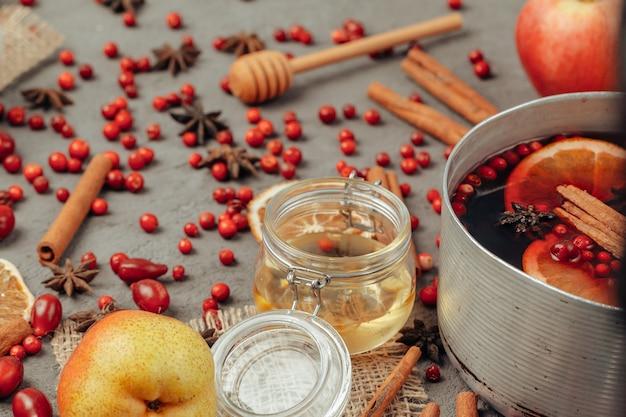 회색 테이블에 향신료와 딸기 mulled 와인 컵 닫습니다