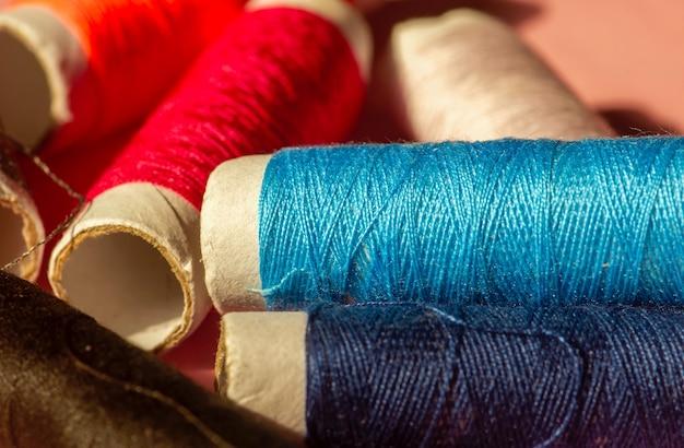 Закройте многоцветные швейные нитки, сосредоточьтесь на голубом цвете