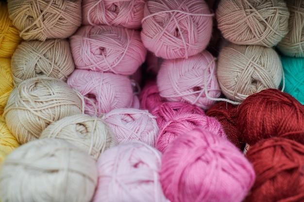 뜨개질 가게 센터에서 여러 가지 빛깔의 원사 공을 닫습니다. 뜨개질을위한 많은 색상 원사. 상점가, 매크로에 다채로운 원사 양모입니다.
