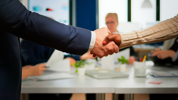 パートナーシップ契約に署名した後、握手する会議デスクの前に立っている多民族のビジネスパートナーのクローズアップ。スタートアップ企業での交渉の成功に満足している多様なチーム