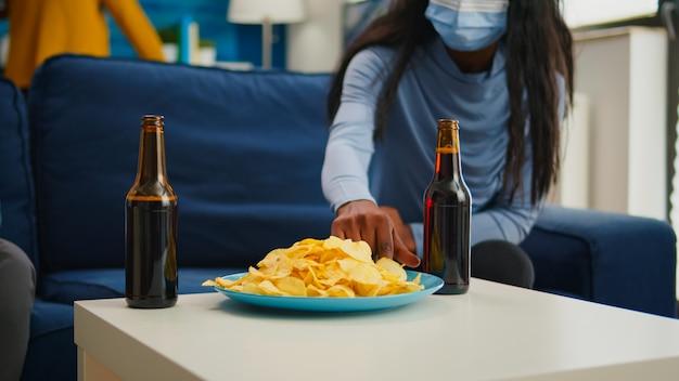 新しい通常のパーティー中にコロナウイルスに対する社会的距離を保ちながら、保護マスクを脱いでスナックを食べる多民族の友人のクローズアップ。世界的大流行の時代に自由な時間を楽しんでいる人々
