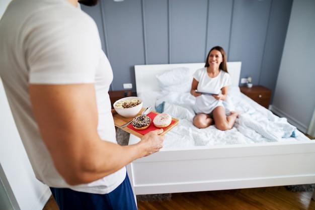 Крупным планом мускулистого мужчины, приносящего завтрак для своей счастливой жены, сидя на кровати с планшетом в пижаме.