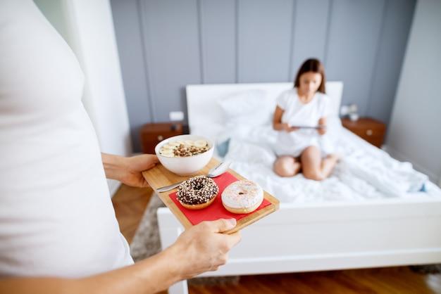 Крупным планом мускулистого мужчины, приносящего пончики и фруктовый салат утром для своей счастливой жены, сидя на кровати с планшетом в пижаме.