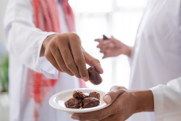 自宅でラマダンの饗宴中に一緒にイフタールディナーを楽しみながら、ナツメヤシの実をとるイスラム教徒の手のクローズアップ