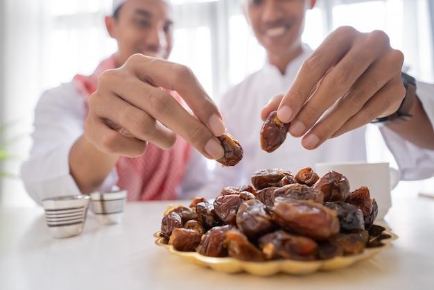 自宅でラマダンの饗宴中に一緒にイフタールディナーを楽しみながら、ナツメヤシの実をとるイスラム教徒の手のクローズアップ Premium写真