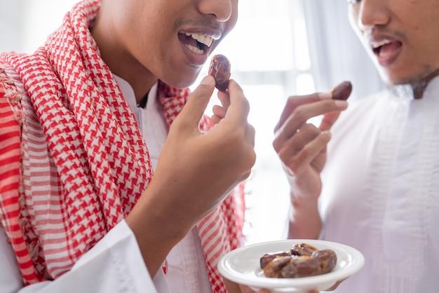 自宅でラマダンの饗宴中に一緒にイフタールディナーを楽しみながら、デートのボウルを共有するイスラム教徒のクローズアップ