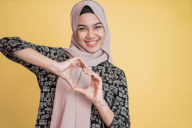 彼女の愛を示す彼女の胸の前で彼女の指でハートジェスチャーをしているイスラム教徒の女性のクローズアップ