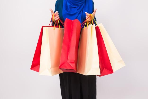 Закройте вверх мусульманской женщины с хозяйственной сумкой на белой предпосылке.