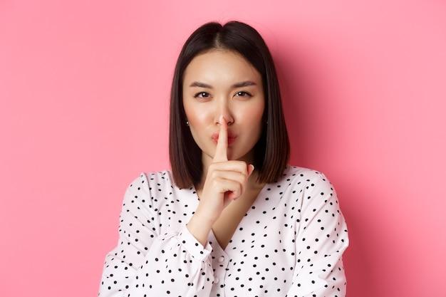 Крупный план загадочной азиатской женщины, скрывающей секрет, замолкающей и говорящей молчать, стоящей над розовым копией пространства