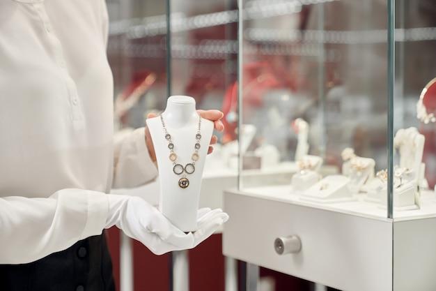 흰 장갑에 여성 조수를 들고 목걸이의 클로즈업