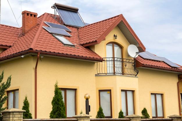 빨간 지붕 널 지붕, 위성 접시, 태양 전지 패널 및 밝은 푸른 하늘 배경에 플라스틱 다락방 창 새로운 벽돌 집 가기의 근접. 부동산 및 전문적으로 완료 된 작업 개념.