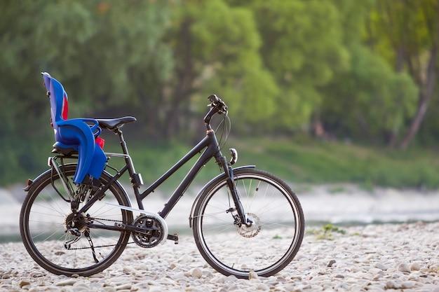Конец-вверх нового современного черного велосипеда при голубое пластичное детское сиденье стоя на бортовой стойке на освещенной камешками солнца на запачканной зеленой предпосылке bokeh лета деревьев. концепция туризма и семейных путешествий.
