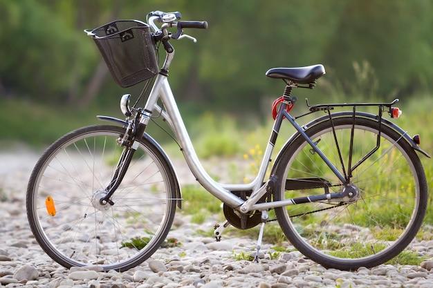 Конец-вверх нового современного белого велосипеда с черными колесами и корзины стоя на стороне стоит на освещенном камешками солнца на запачканном зеленом bokeh лета. удобный транспорт для путешествий концепции.