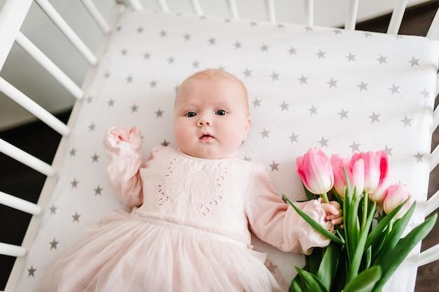 Крупным планом новорожденного девочка рука букет цветов розовых тюльпанов.