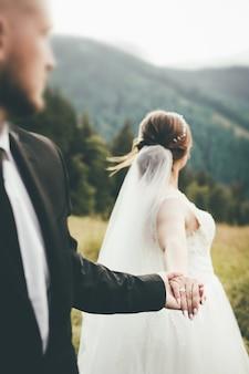 新婚夫婦の手のクローズアップ。新郎新婦が手をつないで山に立ち、コンセプト写真は私に従っています。ぼやけた顔、後ろ姿。高品質の写真