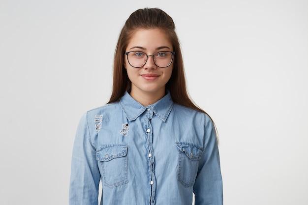 Крупным планом красивая дружелюбная красивая молодая женщина в очках, спокойно стоит