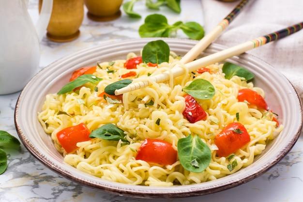 Крупным планом лапши с перцем, листьями салата и кунжутом в тарелку и палочки для еды