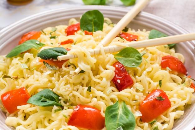Крупным планом лапша с перцем, листьями салата и кунжутом в тарелку и палочки для еды